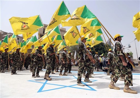 Supporters of Iraqi Hezbollah brigades marching in military uniforms step on a representation of an Israeli flag