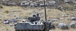 A Turkish soldier stands by a tank as he patrols the border with Syria