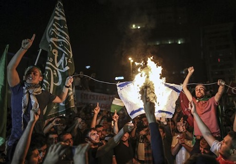 Protesters burn an Israeli flag during a protest rally outside the Israeli consulate in Istanbul, Turkey