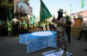 Masked Hamas members prepare to burn a cut-out of a Star of David / AP