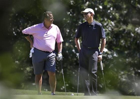 President Barack Obama speaks with golf partner Robert Wolf in Martha's Vineyard /AP