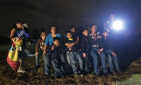A group of immigrants from Honduras and El Salvador who crossed the U.S.-Mexico border illegally as they are stopped in Granjeno, Texas.  /  AP