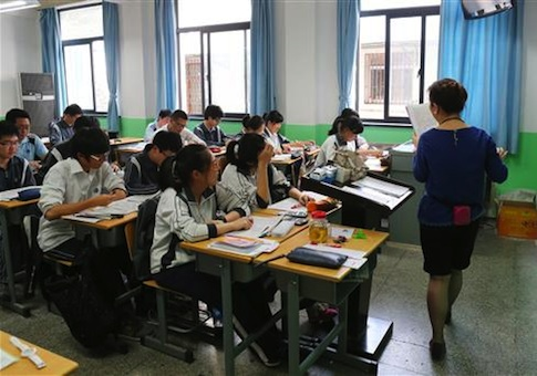 Chinese students listen to a teacher in the preparation for the annual National College Entrance Examination at a school in Shanghai, China