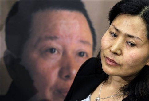Geng He in front of poster of her husband, disappeared Chinese human rights lawyer Gao Zhisheng / AP