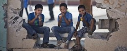 Palestinian school boys drink iced juice as they sit on a damaged wall of a school in Gaza City