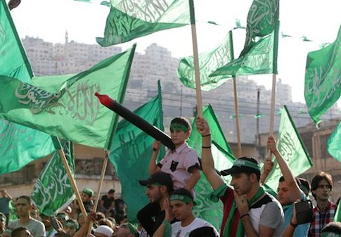 Palestinians hold Hamas flags and chant slogans during a celebration organized by Hamas in the West Bank city of Nablus