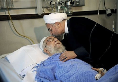 In this picture released by the official website of the office of the Iranian supreme leader, President Hassan Rouhani kisses the forehead of Supreme Leader Ayatollah Ali Khamenei after his surgery at a hospital in Tehran, Iran