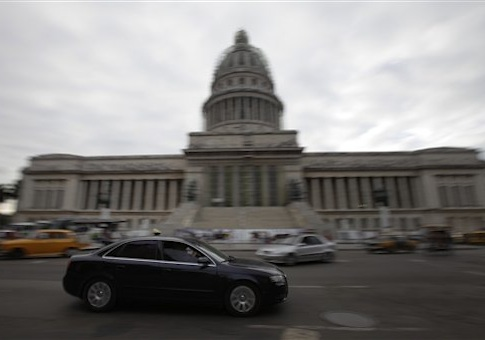 An automobile drives by the Capitol in Havana, Cuba