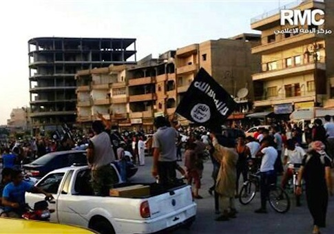 This undated file photo posted by the Raqqa Media Center, a Syrian opposition group, on Monday, June 30, 2014, which has been verified and is consistent with other AP reporting, shows fighters from extremist Islamic State group during a parade in Raqqa, Syria