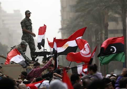 Egyptian army officers guard on top of an armored vehicle as demonstrators wave the Egyptian, Tunisian and Libya's old national flags