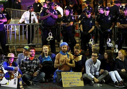 Protesters sit at the intersection of Wall St. and Broad St. in New York, Monday, Sept. 22, 2014