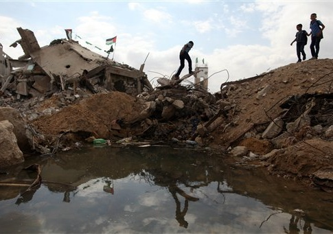 Palestinian students walking next to destroyed houses in Al-Shejaeiya neighbourhood in the east of Gaza City