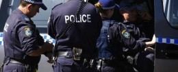 Police talk outside a house that was involved in pre-dawn raids in the western Sydney suburb of Guilford