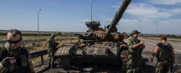 Pro-Russian rebels stand near a burnt-out Ukrainian tank outside the destroyed airport in Luhanks