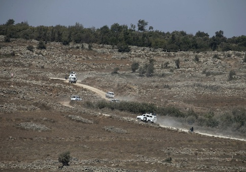 U.N. vehicles drive in Syria near the border fence with the Israeli-occupied Golan Heights