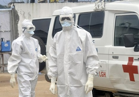 Health workers wearing protective gear wait to carry the body of a person suspected to have died from Ebola, in Monrovia, Liberia