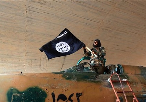 This undated image posted on Aug. 27, 2014 by the Raqqa Media Center of the Islamic State group, a Syrian opposition group, which has been verified and is consistent with other AP reporting, shows a fighter of the Islamic State group waving their flag from inside a captured government fighter jet