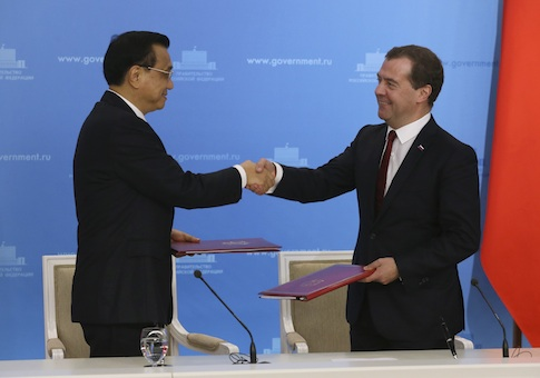 Russia's Prime Minister Dmitry Medvedev (R) shakes hands with China's Premier Li Keqiang during a signing ceremony in Moscow