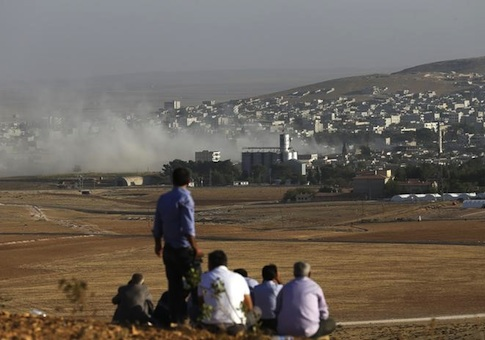 Turkish Kurds look towards the Syrian Kurdish town of Kobani from the top of a hill close to the border line between Turkey and Syria near Mursitpinar