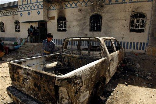 A Yemeni youth looks at a vehicle destroyed during a police raid on a hideout of al-Qaida militants in Arhab region, north of Sanaa, Yemen