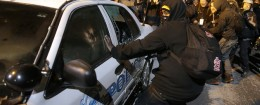 Protesters vandalize a police vehicle near Ferguson City Hall / AP