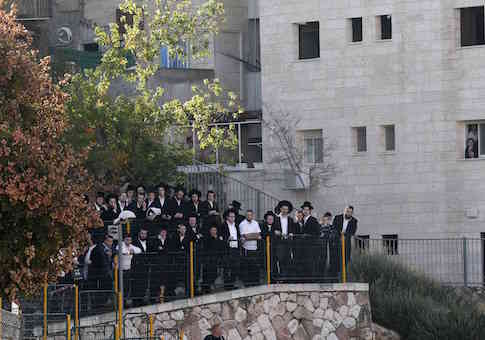 Onlookers stand near the scene of an attack at a Jerusalem synagogue / Reuters