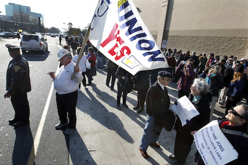 Protester holds a union flag at a 2012 Black Friday OUR Walmart event / AP