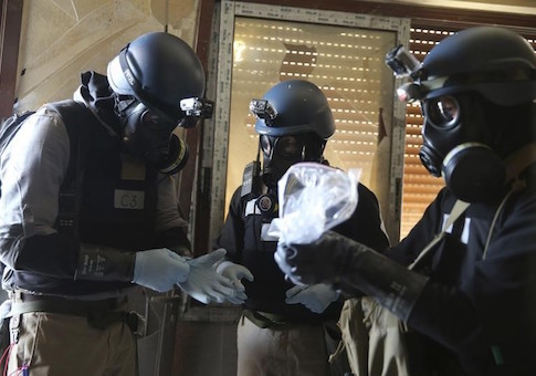A U.N. chemical weapons expert, wearing a gas mask, holds a plastic bag containing samples from one of the sites of an alleged chemical weapons attack in the Ain Tarma neighborhood of Damascus August 29, 2013