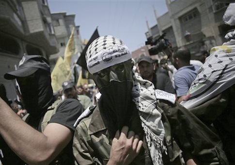 "A masked militant wears a head band with Arabic writing that reads ""the martyr, Abdul Qader Al-Husaini brigades"" during the funeral of two Fatah militants, Marwan Sleem and Mazin Al-Jarba, who were killed by an Israeli airstrike, in Bureij refugee camp, central Gaza Strip, Monday, July, 7, 2014"