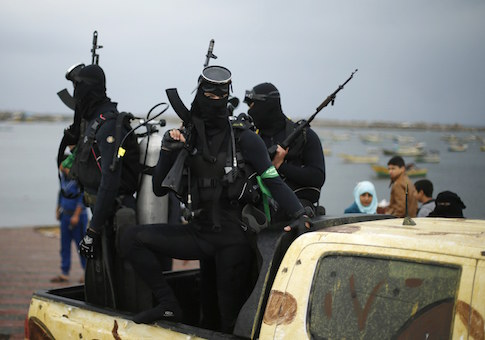 Palestinian members of the marine unit of al-Qassam Brigades, the armed wing of the Hamas movement, ride in a pickup truck as they take part in a military parade marking the 27th anniversary of Hamas' founding, in Gaza City December 14