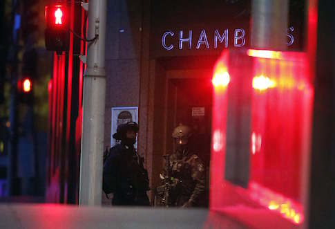 Heavily armed policemen stand guard outside the building containing the Lindt cafe, where hostages are being held, at Martin Place in central Sydney December 16