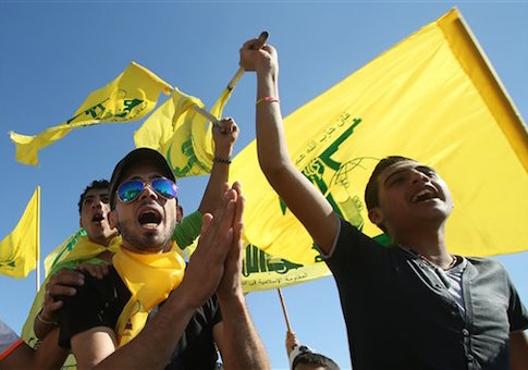 Hezbollah supporters shout slogans and wave Hezbollah flags