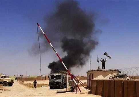 Militants raising the Islamic State flag at the entrance of an army base in Ninevah Province, Iraq