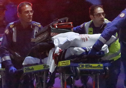 Paramedics remove a person, with bloodstains on the blankets covering the person, on a stretcher from the Lindt cafe, where hostages were being held, at Martin Place in central Sydney December 16
