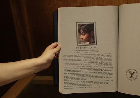 An Israeli worker displays a photo of former Mossad agent Sylvia Rafael in a memorial book in the Intelligence Heritage and Commemoration Center at Gliliot Junction near Tel Aviv