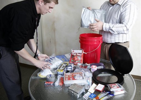 Workers put together emergency preparedness kit / AP