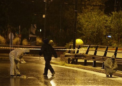 Police forensic experts investigate an area near Israeli Embassy in Athens