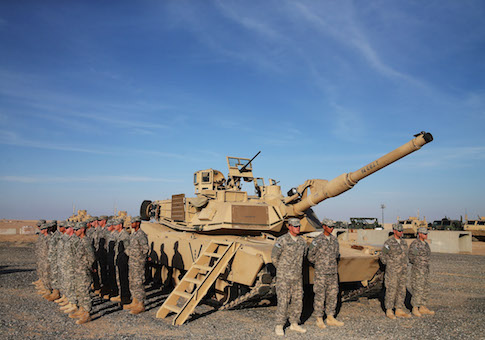 U.S. troops stand at attention next to a Abrams tank waiting for the arrival of Secretary of Defense Chuck Hagel, December 8, 2014 at Camp Buehring, Kuwait