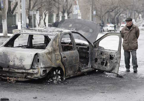A man looks at a burnt car near a trolleybus stop in Donetsk, January 22, 2015