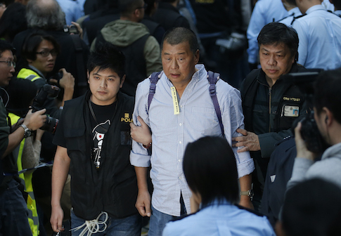 Hong Kong media magnate Jimmy Lai is taken away by police officers during protests last year / AP