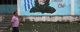 "A man walks past near an image of revolutionary hero Ernesto ""Che"" Guevara in Havana December 27, 2014"