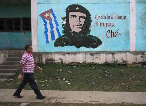 "A man walks past near an image of revolutionary hero Ernesto ""Che"" Guevara in Havana December 27, 2014"