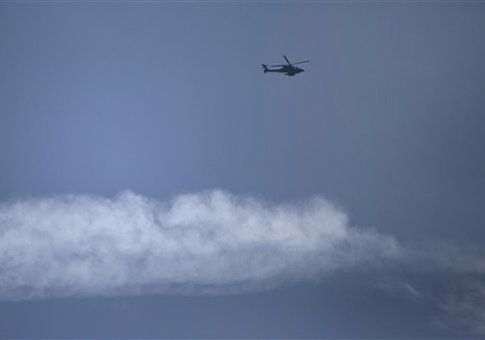An Israeli helicopter flies over the Israel-Lebanon border, Wednesday, Jan. 28, 2015