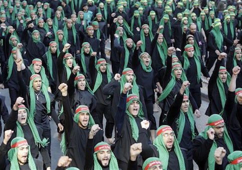 Lebanese Hezbollah supporters shout slogans as they march during Ashoura day in Beirut's southern suburbs, Lebanon, Tuesday, Dec. 6, 2011