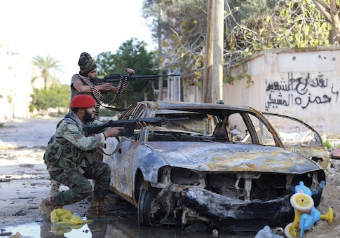 Pro-government Libyan forces, who are backed by locals, aim their weapons during clashes in the streets with the Shura Council of Libyan Revolutionaries, an alliance of former anti-Gaddafi rebels, who have joined forces with the Islamist group Ansar al-Sharia, in Benghazi December 28
