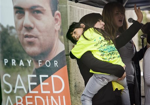 Nagmeh Abedini holds her daugher Rebekka Grace Abedini, 7, during a prayer vigil at the Idaho Statehouse in Boise Thursday Sept. 26, 2013