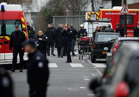 Police officers and firemen gather outside the French satirical newspaper Charlie Hebdo's office, in Paris, Wednesday, Jan. 7