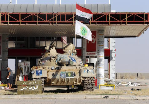 A tank belonging to the Shi'ite Badr Brigade militia takes position in front of a gas station in Suleiman Beg, northern Iraq in this September 9, 2014