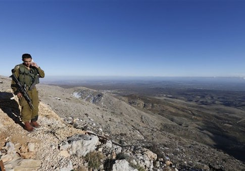 An Israeli soldier speaks on his mobile phone at a military outpost at Mount Hermon in the Israeli-controlled Golan Heights overlooking the Israel-Syria border on Wednesday, Feb. 4, 2015