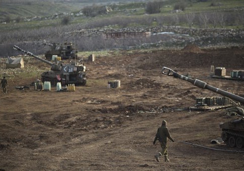 Israeli soldiers walk next to mobile artillery units in the Israeli-controlled Golan Heights near the border with Syria, Wednesday, Jan. 28, 2015